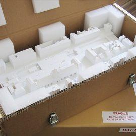 caisse en carton avec un armature bois contenant une maquette d'architecture